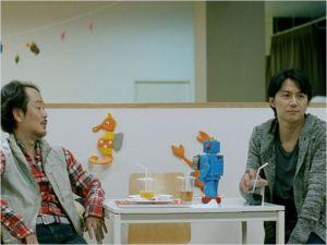 l'2picier  ( Lily Franky)  et  Ryota ( Masaharu  Fukuyama )  en pleine  conversation  sur  leurs  progéniture