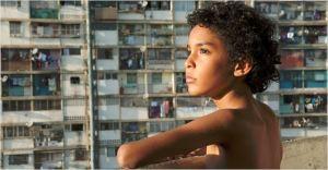 Junior ( Samuel Lange )   sur  son balcon face  aux  immeubles de  la cité