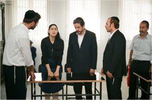 Une scène du  tribunal .  Viviane  ( Ronitez  Elkabetz )  et  son avocat ( Menashey  Noy )  face  a deux  témoins  .  A  droite  ,  le   frère   ( Sasson Gabai  )  et  défenseur  du mari