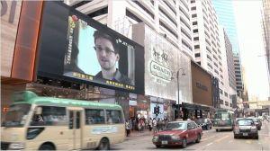 Le  sacnadale  éclate , les images de l'interview de  Snowden  sur  les écrans dans  la rue