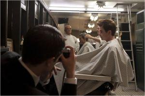 Le reportage commence : séance chez le coiffeur . Robert Pattinson ( de dos ) et Dane DeHaan .