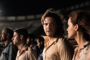 Léna ( Emma watson) et Daniel ( Dabiel Brûhl ) en compagnie des ajtres prisonniers au stade de santiago du Chili
