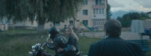Eliza sur la moto en compagnie de son petit ami, sous le regard de son père